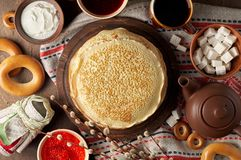 Shrovetide Maslenitsa Butter Week festival meal. Stack of russian pancakes blini. With red caviar, fresh sour cream, cranberry jam and sushki. Rustic style stock photography
