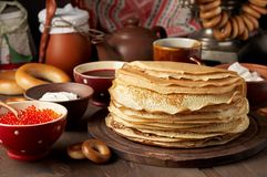 Shrovetide Maslenitsa Butter Week festival meal. Stack of russian pancakes blini. With red caviar, fresh sour cream and cranberry jam. Rustic style, close up royalty free stock images