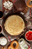 Shrovetide Maslenitsa Butter Week festival meal. Stack of russian pancakes blini. With red caviar, fresh sour cream, cranberry jam and sushki. Rustic style royalty free stock image