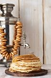 Shrovetide Maslenitsa Butter Week festival meal. Stack of russian pancakes blini. On the background of samovar with sushkie. Rustic style, close up view with stock photography