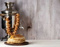 Shrovetide Maslenitsa Butter Week festival meal. Stack of russian pancakes blini. On the background of samovar with sushkie. Rustic style, close up view with royalty free stock photos