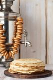 Shrovetide Maslenitsa Butter Week festival meal. Stack of russian pancakes blini. On the background of samovar with sushkie. Rustic style, close up view with royalty free stock photo