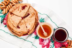 Shrovetide Maslenitsa festival meal. Russian pancake blini with honey and fresh cream cheese on white background. Top view. Flat lay royalty free stock photo