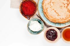 Shrovetide Maslenitsa festival meal. Russian pancake blini with raspberry jam, honey, fresh cream and red caviar on white background stock photo
