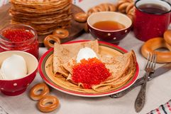 Shrovetide Maslenitsa festival meal. Russian pancakes blini with honey, fresh cream cheese and red caviar. Rustic style royalty free stock photography