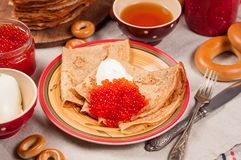 Shrovetide Maslenitsa festival meal. Russian pancakes blini with honey, fresh cream cheese and red caviar. Rustic style stock images