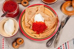 Shrovetide Maslenitsa festival meal. Russian pancakes blini with honey, fresh cream cheese and red caviar. Rustic style royalty free stock image
