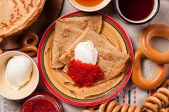 Shrovetide Maslenitsa festival meal. Russian pancakes blini with honey, fresh cream cheese and red caviar. Rustic style royalty free stock photos