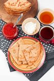 Shrovetide Maslenitsa festival meal. Russian pancakes blini with honey, fresh cream cheese and red caviar on white background stock images