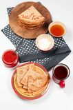 Shrovetide Maslenitsa festival meal. Russian pancakes blini with honey, fresh cream cheese and red caviar on white background stock photos