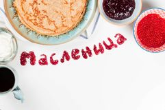 Shrovetide Maslenitsa festival meal. Russian pancake blini with raspberry jam, fresh cream and red caviar on white background stock photography