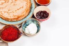 Shrovetide Maslenitsa festival meal. Russian pancake blini with raspberry jam, honey, fresh cream and red caviar on white background royalty free stock images