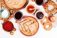 Shrovetide Maslenitsa festival meal. Russian pancake blini with raspberry jam, honey, fresh cream and red caviar on white background royalty free stock photo