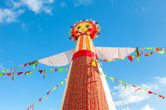 Shrovetide in Russia. Big doll for the burning on the blue sky b Royalty Free Stock Photo