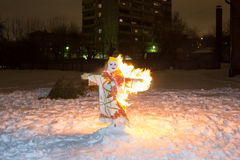 Shrovetide scarecrow burnes at night in snow Stock Image