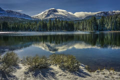 Shrubs and Lassen Peak after snow storm with reflections in Manzanita Lake, Lassen Volcanic National Park Stock Photo