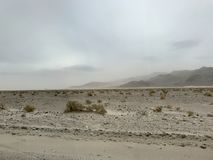 Dusty Storm in Desert with Mountains in Background. Shrubs line the view of Desert from road side on cloudy day. Sand storm beginning to form Royalty Free Stock Photography