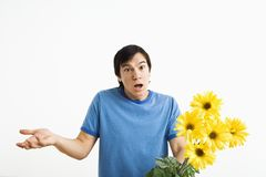 Shrugging man holding bouquet. Asian young man holding bouquet of yellow gerber daisies shrugging royalty free stock photos