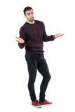 Shrugging young clueless man looking at camera with spread arms. Full body length portrait isolated over white background royalty free stock photo