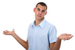 Shrugging young man in blue shirt isolated Royalty Free Stock Photo