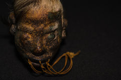 A shrunked human head from ecuador over a dark background Royalty Free Stock Image