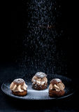 Shu cake sprinkled with powdered sugar on a black background Royalty Free Stock Photo