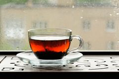 Shu puerh tea brewed in glass cup on window sill Royalty Free Stock Photo