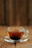 Shu puerh tea brewed steaming in glass cup on wooden background Royalty Free Stock Photos