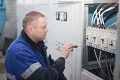 SHUCHIN BIAŁORUŚ, STYCZEŃ, - 26, 2015 Fachowy elektryk instaluje składniki w elektrycznej osłonie Zdjęcie Stock