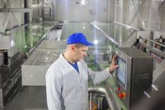 SHUCHIN VITRYSSLAND - JANUARI 26, 2015 man arbetarfungerande produktionslinjen på ostfabriken arkivfoton