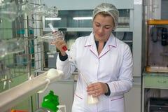 SHUCHIN, WEISSRUSSLAND - 26. JANUAR 2015 Junge Frau im chemischen Labor, das mikrobiologische und chemische Qualitätskontrolle vo Lizenzfreie Stockfotos