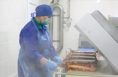 SHUCHIN, WIT-RUSLAND - JANUARI 26, 2015 De vrouw is bezig geweest met de verpakking van kaas op een kaasfabriek Stock Foto