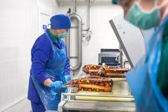 SHUCHIN, WIT-RUSLAND - JANUARI 26, 2015 Vrouwen belast met de verpakking van kaas op een kaasfabriek Stock Foto