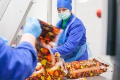 SHUCHIN, WIT-RUSLAND - JANUARI 26, 2015 Vrouwen belast met de verpakking van kaas op een kaasfabriek Royalty-vrije Stock Afbeelding