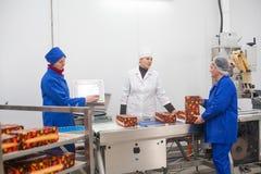 SHUCHIN, WIT-RUSLAND - JANUARI 26, 2015 Vrouwen belast met de verpakking van kaas op een kaasfabriek Royalty-vrije Stock Afbeeldingen