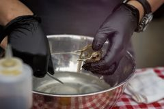 Shucking fresh oysters, man`s hands in black gloves with knife and on a seafood market. Gastronomic gourmet dainty. Products on market counter, real scene in royalty free stock images