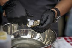 Shucking fresh oysters on a seafood market. Man`s hands in black gloves with knife. Gastronomic gourmet dainty products. Shucking fresh oysters on a seafood stock photography