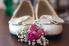 Shues de la novia con las flores en la tabla imagen de archivo