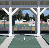 Shuffleboard Court. Sports or rec center with shuffleboard court in the front and some children playing basketball in the far court stock photo