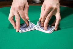 Shuffling cards. Dealer shuffle cards in casino over green felt royalty free stock image