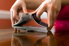 Shuffling a Deck of Cards on a Reflective Table stock photo