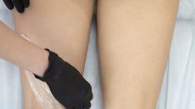 Рука мастерский shugaring для приложения особенного воска на ногах девушек и острых движениях, он слезает его назад акции видеоматериалы