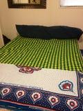 Shuka e kanga de Maasai sobre uma cama Imagens de Stock