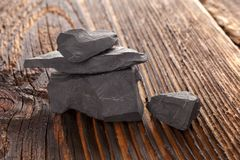 Shungit stone. Shungit stone on dark wooden background. Natural water cleaner stock images