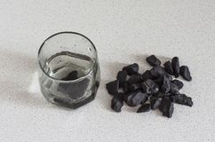 The shungite stones in a glass of water.the concept of cleansing the body royalty free stock photo
