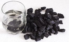 Shungite stones in a glass for water purification and recharge.  stock photos