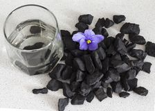 Shungite stones in a glass of water to clean and recharge water ,close-up view from above royalty free stock photos