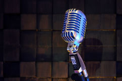 SHURE Super 55 Deluxe. MINSK, BELARUS - SEPTEMBER 29, 2015: Silver old fashioned stage microphone- SHURE Super 55 Deluxe against wood background. Room for sound Stock Images
