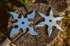 Shuriken throwing star, traditional japanese ninja cold weapon. Stuck in wooden background royalty free stock image