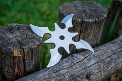 Shuriken throwing star, traditional japanese ninja cold weapon. Stuck in wooden background royalty free stock photos